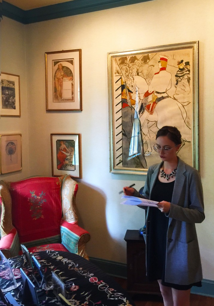 Sarah Shelburne of the Vintage Posters department takes notes in the living room in front of Babylone d'Allemagne by Henri de Toulouse-Lautrec.