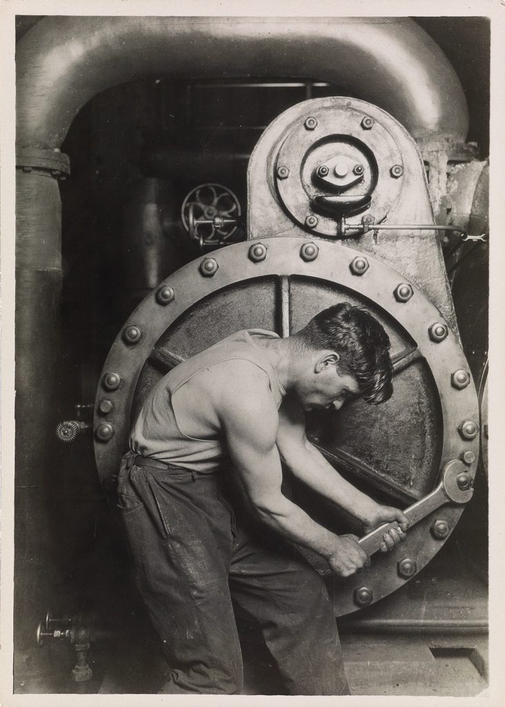 Black and white photograph of a man tightening a bold by Lewis Hine.