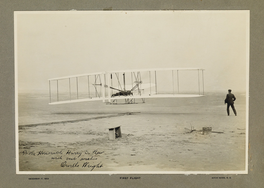 silver print of an image showing the first flight of the Wright Flyer I in 1903 with Orville Wright piloting and Wilbur running alongside.