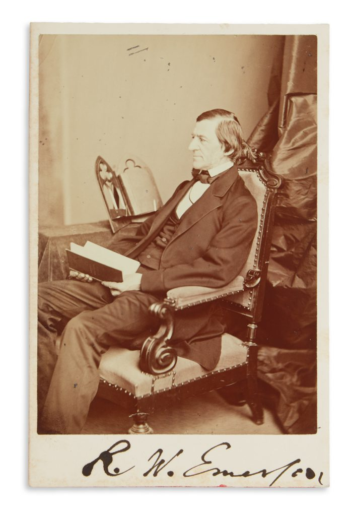Lot 324, signed photograph of Ralph Waldo Emerson sitting in a chair with a book.