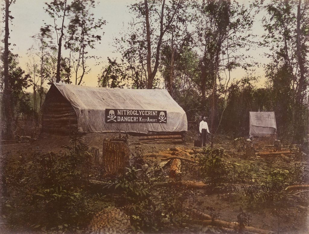 A hand-colored photograph of red river raft which features the brush and swamp of Louisiana with fallen trees surrounding a log cabin with a tarp over the roof that reads NITROGLYCERIN! DANGER! KEEP AWAY! with a man standing in front.