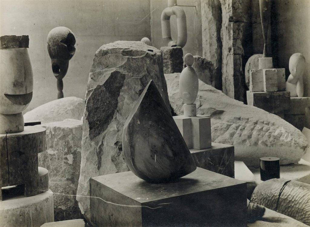 A black and white photograph by Constantine Brancusi of four of his most iconic sculptures in his studio.