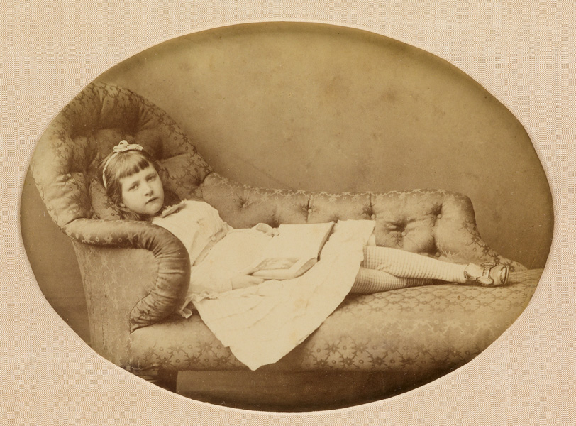 sepia portrait of a little girl reading on a couch