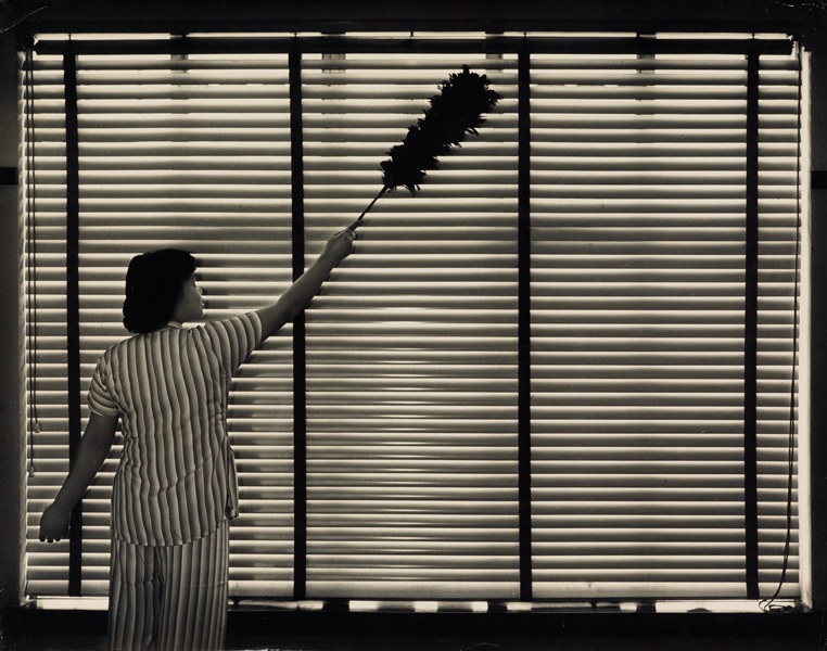 monochrome portrait of a woman cleaning window blinds