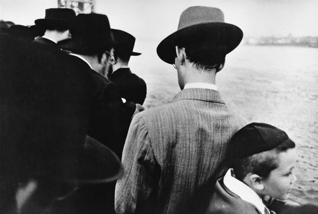 Black and white photo of Jewish men and a young boy on a ferry in New York in 1955 by Robert Frank.