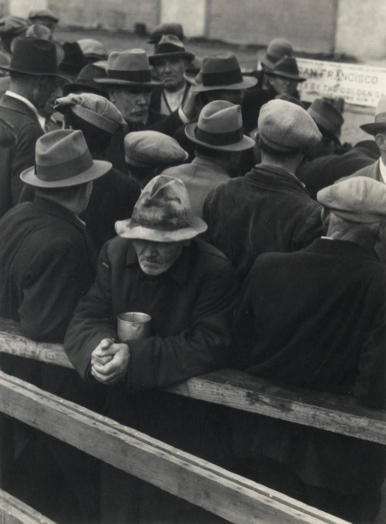 Black and white image of men waiting in a breadline during the Great Depression by Dorothea Lange.