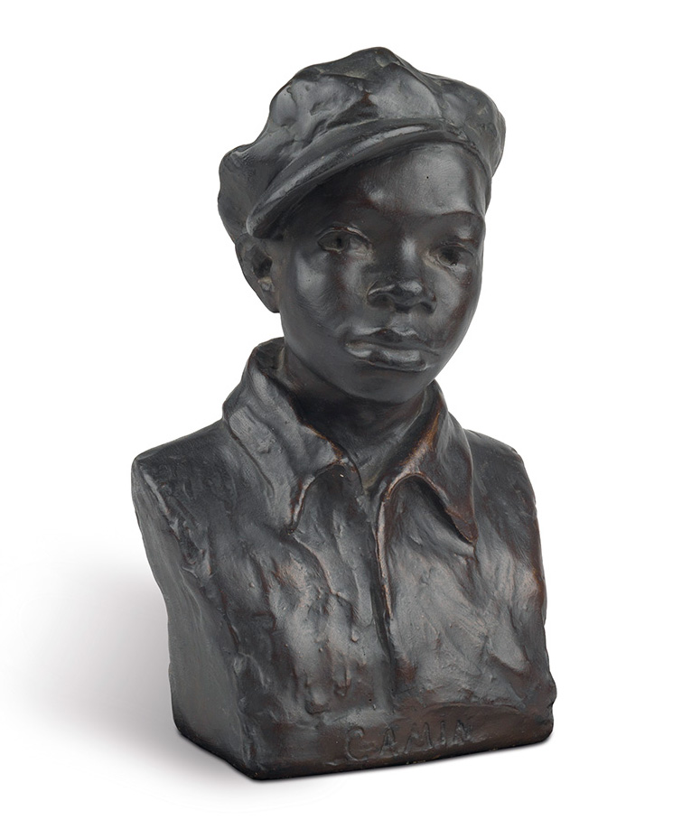 A bust sculpture of a young boy in a news cap.