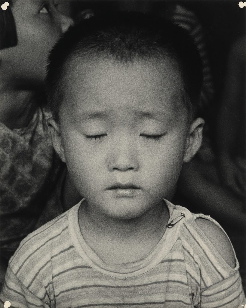 Black and white photograph of a small Korean child by Dorothea Lange