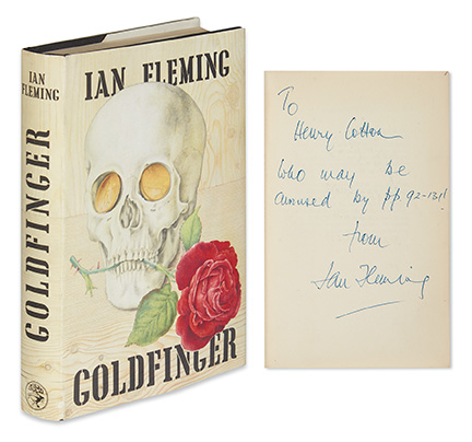 "Cover of Ian Fleming's ""Goldfinger,"" with a skull and a rose on it, shown with inscription page."