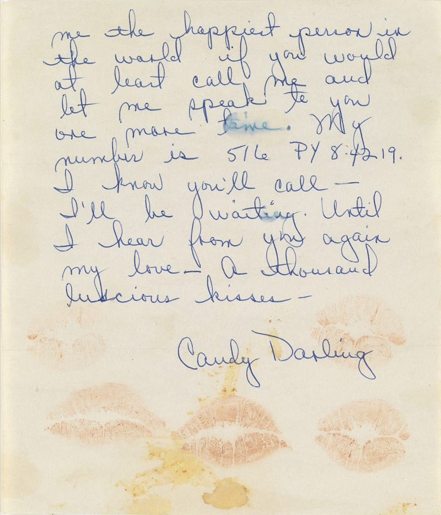 A handwritten letter in blue ink by Candy Darling with lipstick kisses at the bottom.