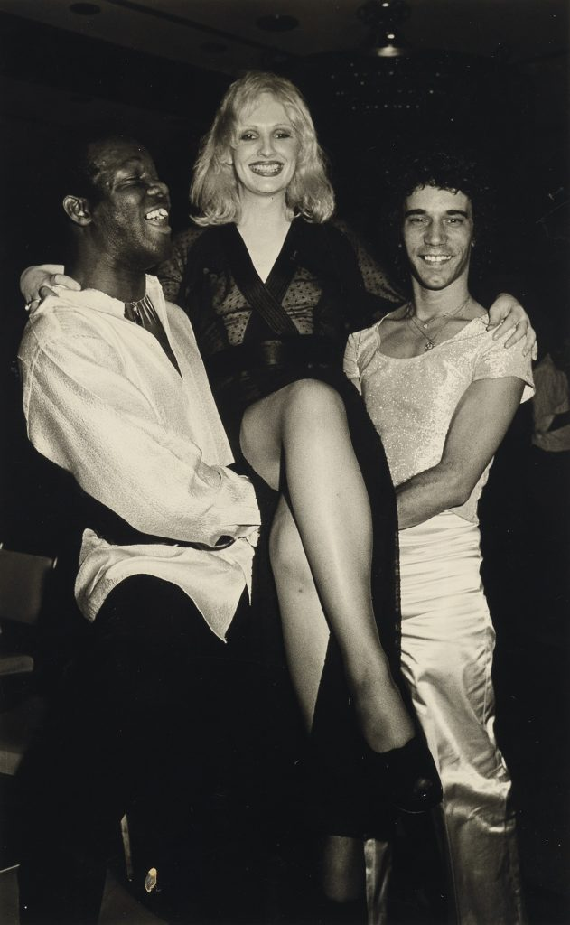 Black and white photograph of Candy Darling being carried