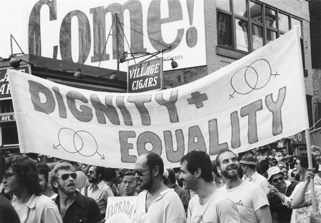 "Photograph of parade goers at a NYC Pride parade in front of Village Cigars with a sign that reads ""Dignity + Equality."""