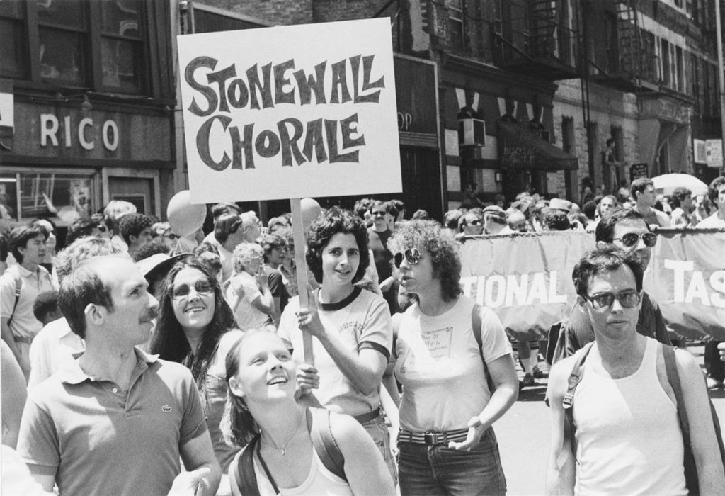 "Photograph of parade goers at a NYC Pride parade with a sign that reads ""Stonewall Choral."""