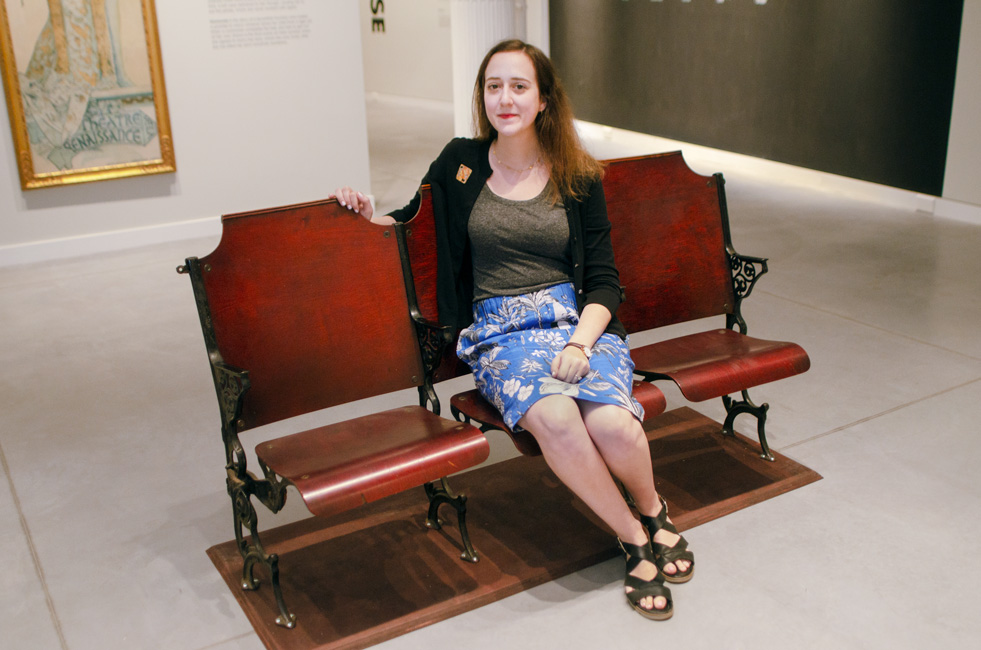 Lauren Goldberg sits in old theater chairs at the Poster House museum's Alphonse Mucha exhibition.