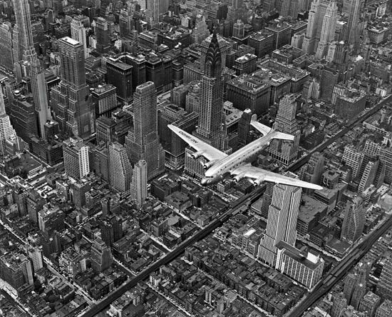 Margaret Bourke-White, DC-4 Flying Over New York City, silver print photograph of an airplane mid-flight over NYC, 1939.