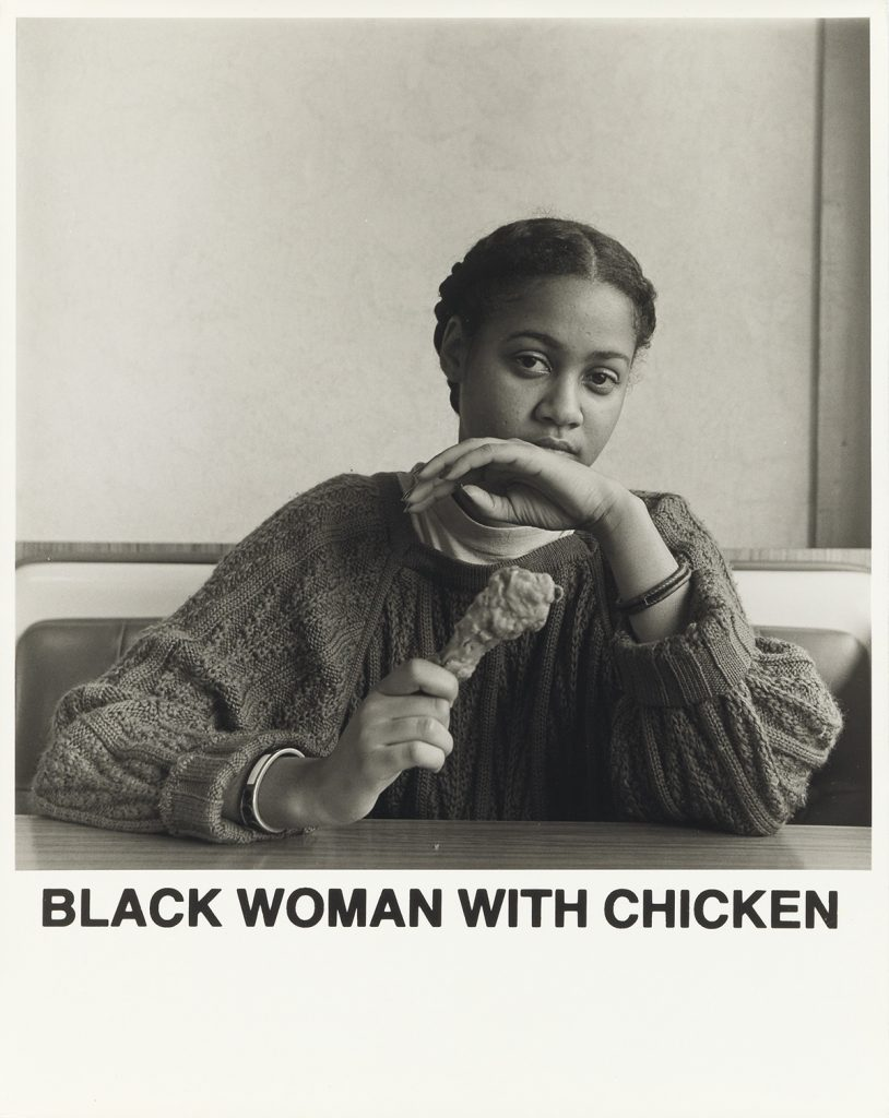 "Carrie Mae Weems, Black Woman with Chicken, black and white silver print of a woman holding a chicken leg, with text that reads ""Black Woman with Chicken,"" 1987."