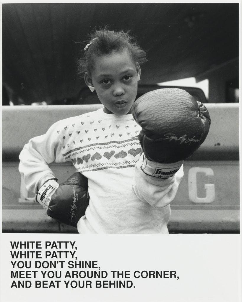 "Carrie Mae Weems, White Patty, silver print of a little girl with boxing gloves held up, with text that reads ""White Patty, White Patty, You Don't Shine, Meet You Around the Corner and Beat Your Behind,"" 1987."