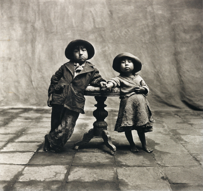 Irving Penn, Cuzco Children, Peru, December, platinum-palladium print of a little boy and girl standing holding hands across a table, 1948.