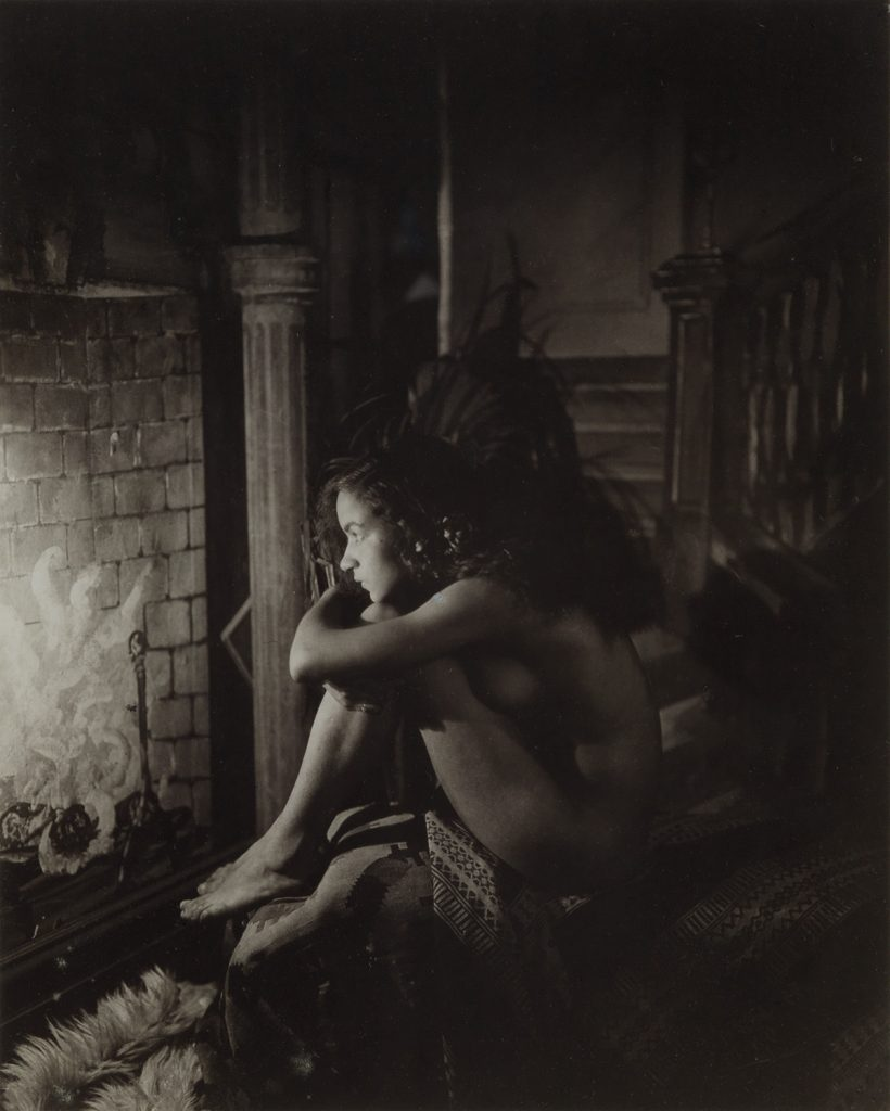James Van Der Zee, Nude, Harlem, silver print of a nude woman looking at a fireplace, 1923.