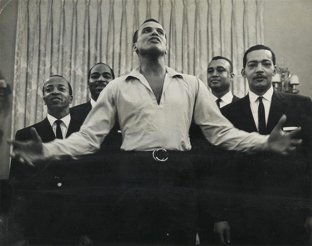Roy DeCarava, Untitled (Harry Belafonte, Carnegie Hall), black and white silver print of Harry Belafonte singing with arms spread wide with four backup singers behind him, 1960.