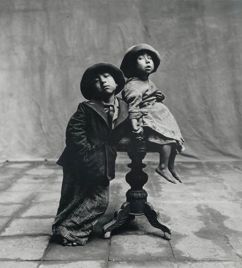 Irving Penn, Cuzco Children, Cuzco, black and white silver print of a little boy and girl with the little girl sitting on a table, 1948.